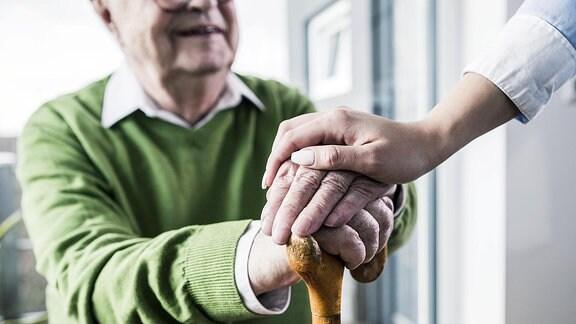 Die Hand einer Frau hält die Hand eines älteren Mannes.