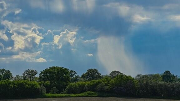 Dunkle Regenwolken ziehen über die Landschaft.