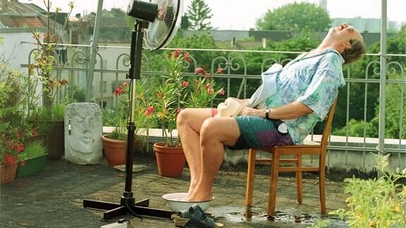 Mann kühlt sich auf seiner Terrasse mit einem Ventilator ab
