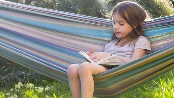 Mädchen sitzt lesend in einer Hängematte