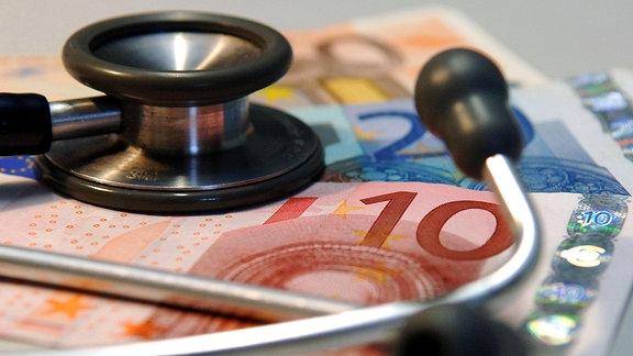 Ein Stethoskop liegt 2005 auf mehreren Geldscheinen.