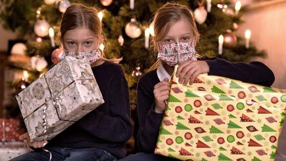 Zwei Kinder mit Masken und Gecshenken vor Weihnachtsbaum