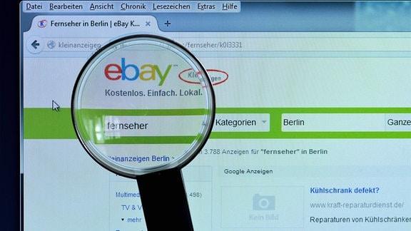 ebay Kleinanzeigen auf einem Bildschirm, davor eine Lupe.