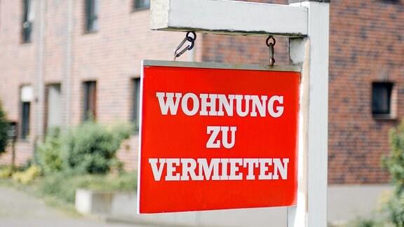 """Rotes Aushängeschild """"Wohnung zu vermieten"""" vor einem Mietshaus."""