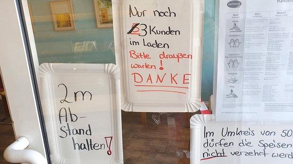 Handschriftlicher Schilderwald mit Zugangsbeschränkungen und Hygienevorschriften an einem Geschäft