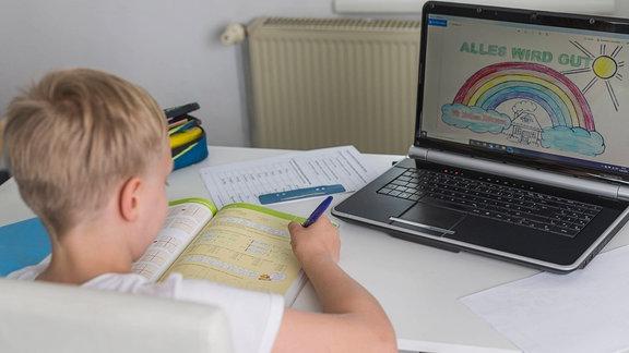 Ein Junge arbeitet an seinen Aufgaben und hat einen Laptop aufgeklappt.