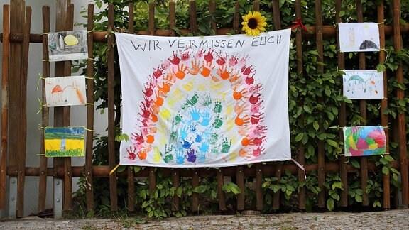 Kindermalereien und ein Banner mit der Aufschrift Wir Vermissen Euch hängen am Kinderhaus Pittiplatsch in Potsdam-Babelsberg