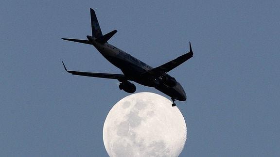 Silhouette eines Flugzeugs vor Vollmond