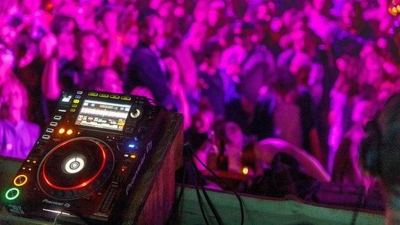 DJ-Pult vor Tanzpublikum