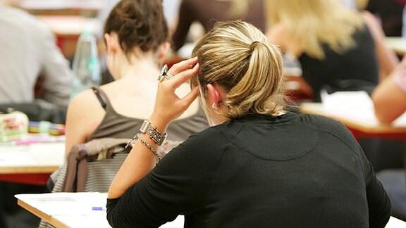 Schüler sitzen mit dem Rücken zum Betrachter in einer Prüfung