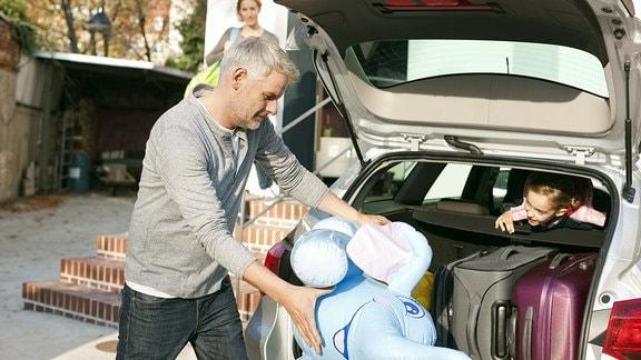 Ein Mann versucht, ein großes Plüschtier im bereits beladenen Kofferraum unterzubringen.
