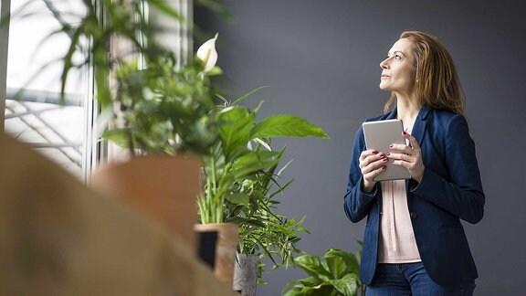 Frau steht neben einem Fensterbrett voller Pflanzen