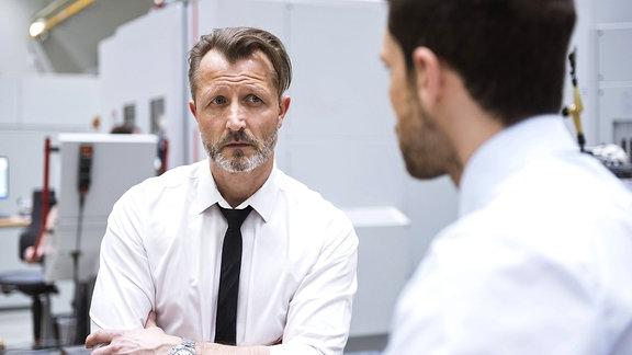 Zwei Männer unterhalten sich in einer Fabrikhalle