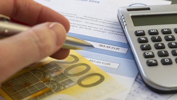 Hand mit Stift, 200-Euro-Schein und Taschenrechner