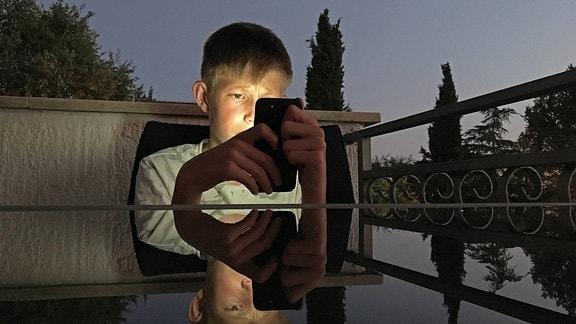 Schulkind schaut gebannt auf ein Smartphone und liest.