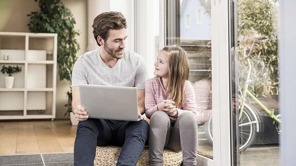 Ein Vater sitzt mit seiner Tochter am Laptop.