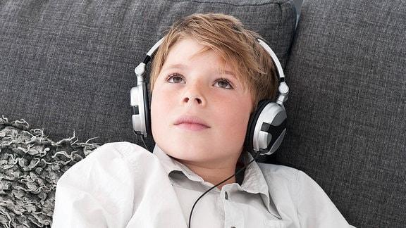Ein Junge liegt mit Kopfhörern auf einem Sofa