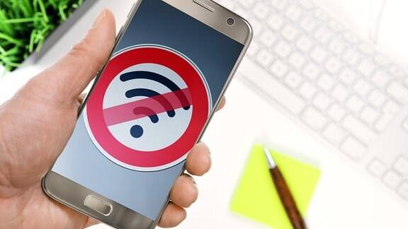 Hand hält Smartphone mit durchgestrichenem WLAN-Symbol