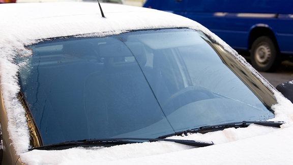 Frontscheibe eines verschneiten Autos ist frei gewischt