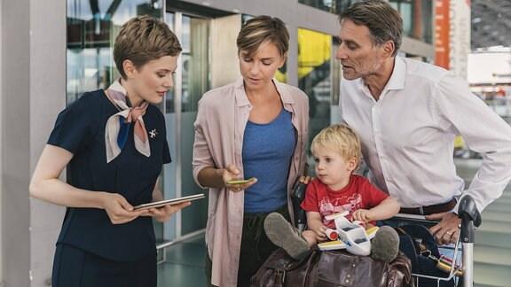 Angestellte einer Fluggesellschaft hilt einer Familie mit Gepäck.