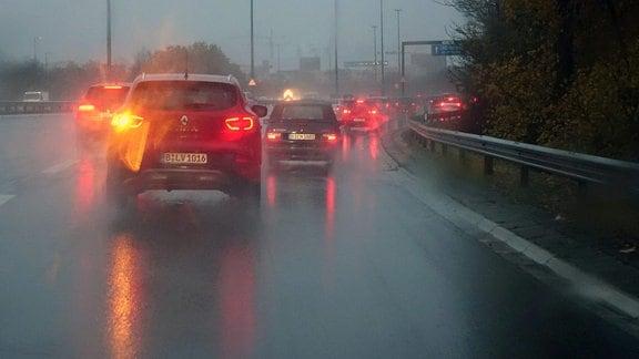 Auto blinkt bei Regen auf der Fahrbahn.