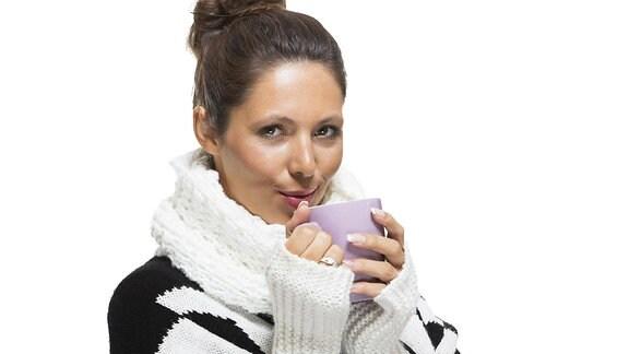 Eine Frau mit Pulswärmern und einer Tasse Tee