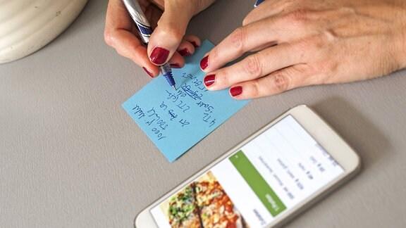 Frau schreibt eine Einkaufsliste vom Rezept ab
