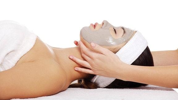 Junge Frau mit Gesichtsmaske im Kosmetiksalon bekommt Kopfmassage.