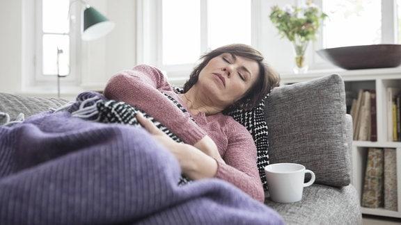 Eine Frau liegt mit Bauchschmerzen auf einem Sofa.