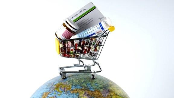 Einkaufswagen gefüllt mit verschiedenen Medikamenten steht auf einem Globus