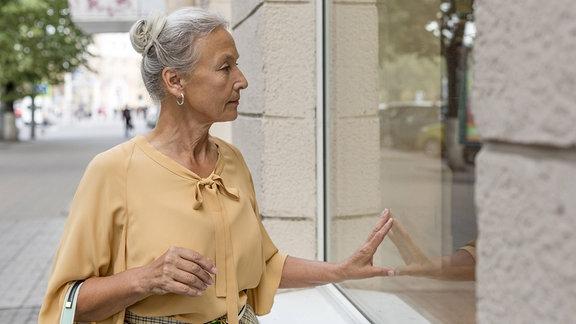 Ältere Frau vor einem Schaufenster.