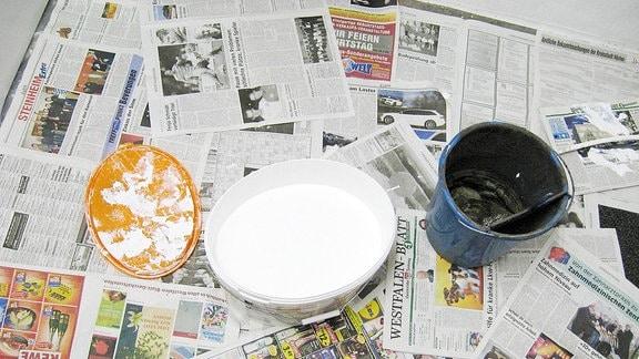 Farbeimer mit weißer und schwarzer Farbe stehen auf ausgelegtem Zeitungspapier.