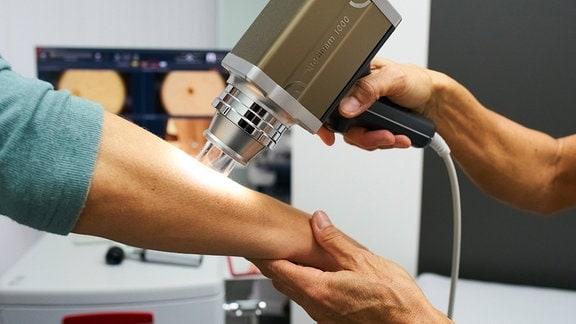 Hautarzt führt ein Hautkrebsuntersuchung mit einer Spezialkamera durch.