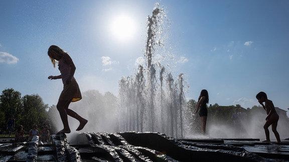 Kinder spielen bei Hitze an einem Springbrunnen