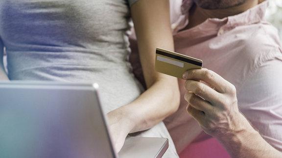 Ein Paar sitzt mit einer Kreditkarte vorm Laptop.