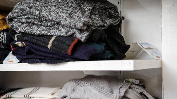 Mottenfalle neben Wollpullovern in einem Kleiderschrank