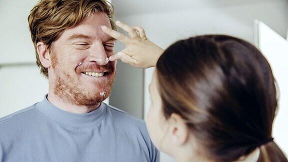 Einem Mann wird von einer Frauenhand Creme an die Nase getupft.
