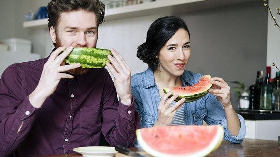 Ein junges Paar genießt am Küchentisch sitzend  Wassermelone.