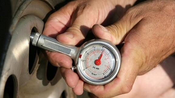 Mann prüft mit einem Luftdruckmesser den Druck auf einen Reifen
