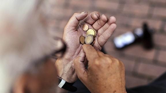 Rentner zählt Geld in seiner Hand