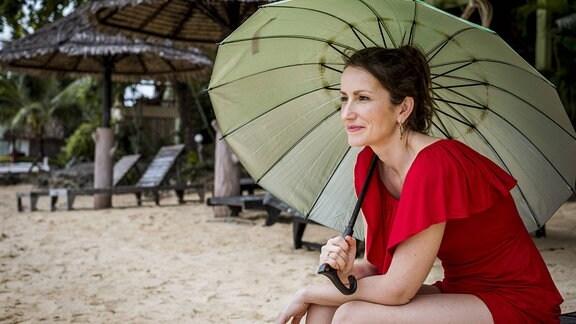 Frau unter Sonneschirm am Strand