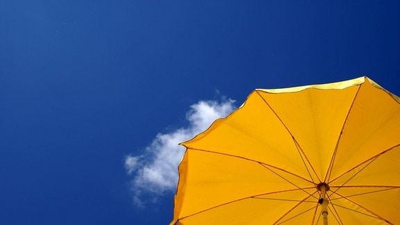 Gelber Sonnenschirm vor blauem, fast wolkenlosem Himmel