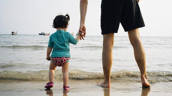 Kind mit UV-Schutz-T-Shirt an der Hand seines Vaters am Strand