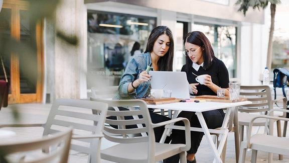 Zwei junge Frauen sitzen im Café am Laptop.
