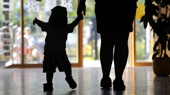Ein kleines Kind wird in einem Kindergarten von einer Kindergärtnerin an der Hand geführt.