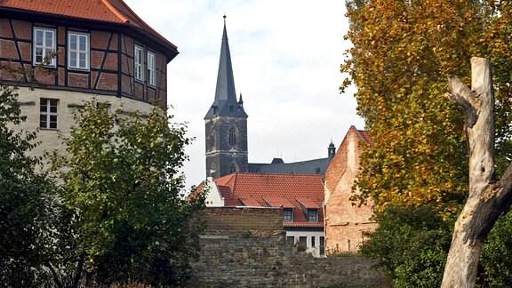 Alte Mauern in der Altstadt von Aschersleben, dahinter der Turm der Stephanikirche.