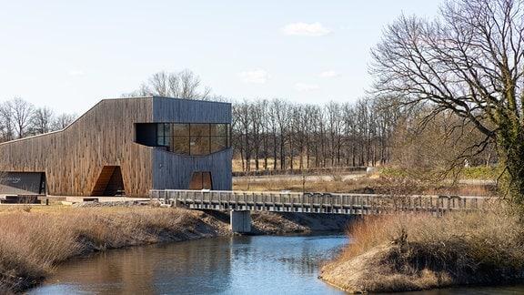 Blick auf ein futuristisches Gebäude an einem Fluss.
