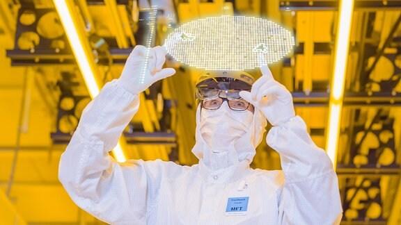 Ein Mann in weißem Overall und Handschuhen steht vor einem transparenten Bildschirm und berührt ihn, der Hintergrund ist gelb.