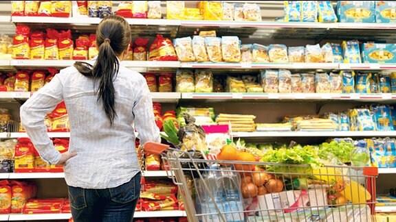 Eine junge Frau steht mit einem vollen Einkaufswagen vor einem Supermarktregal
