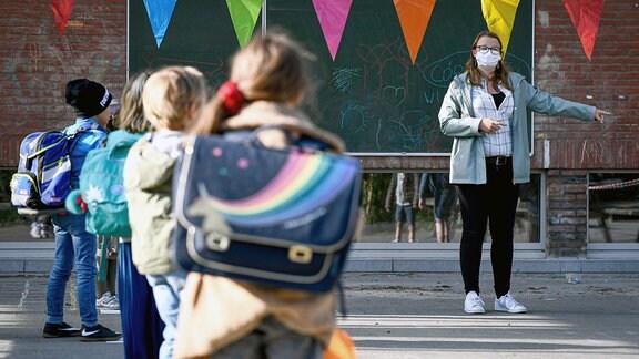 Eine Lehrerin mit Maske erklärt Schülern etwas.
